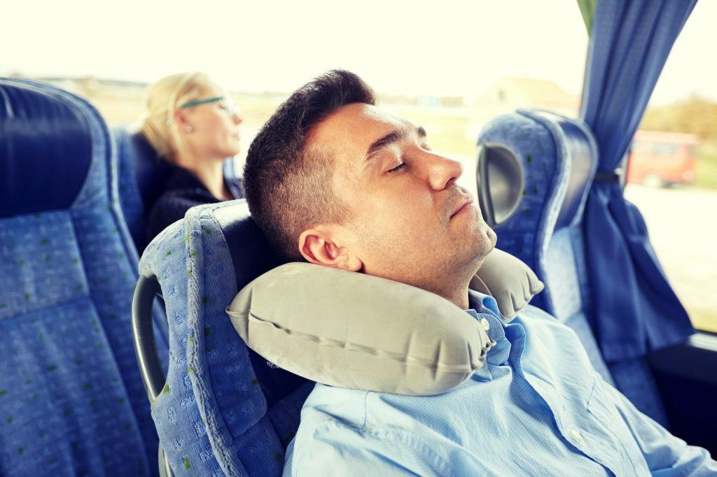 man sleeping in travel bus with cervical pillow