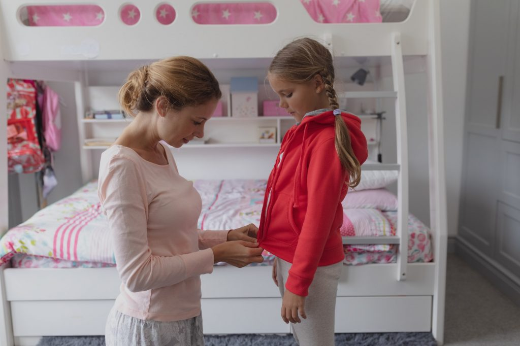 Side view of Caucasian mother helping daughter putting on clothes in bedroom at comfortable home